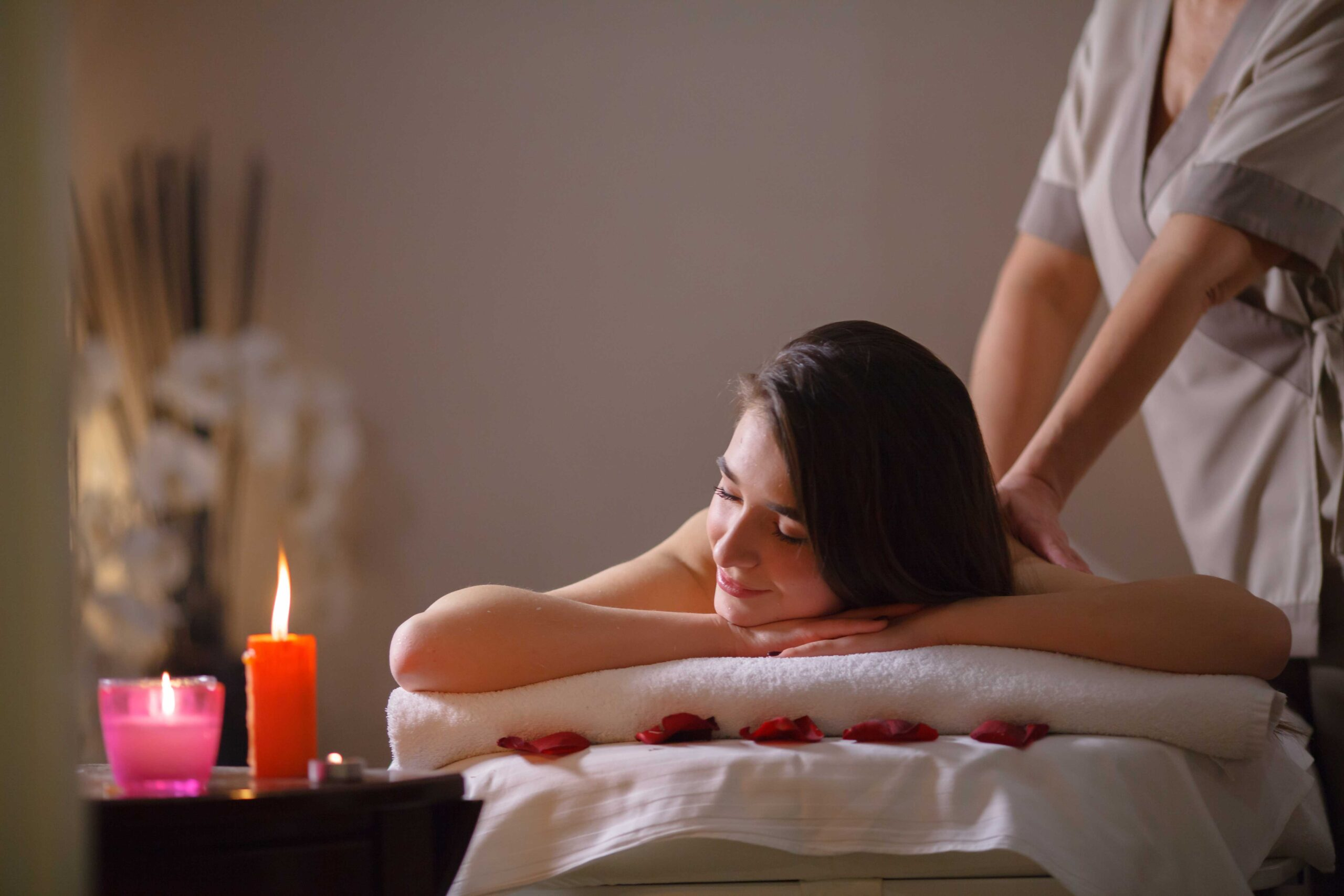 A woman getting a Balinese massage with the gentle hands of a professional masseur in a serene environment of a spa
