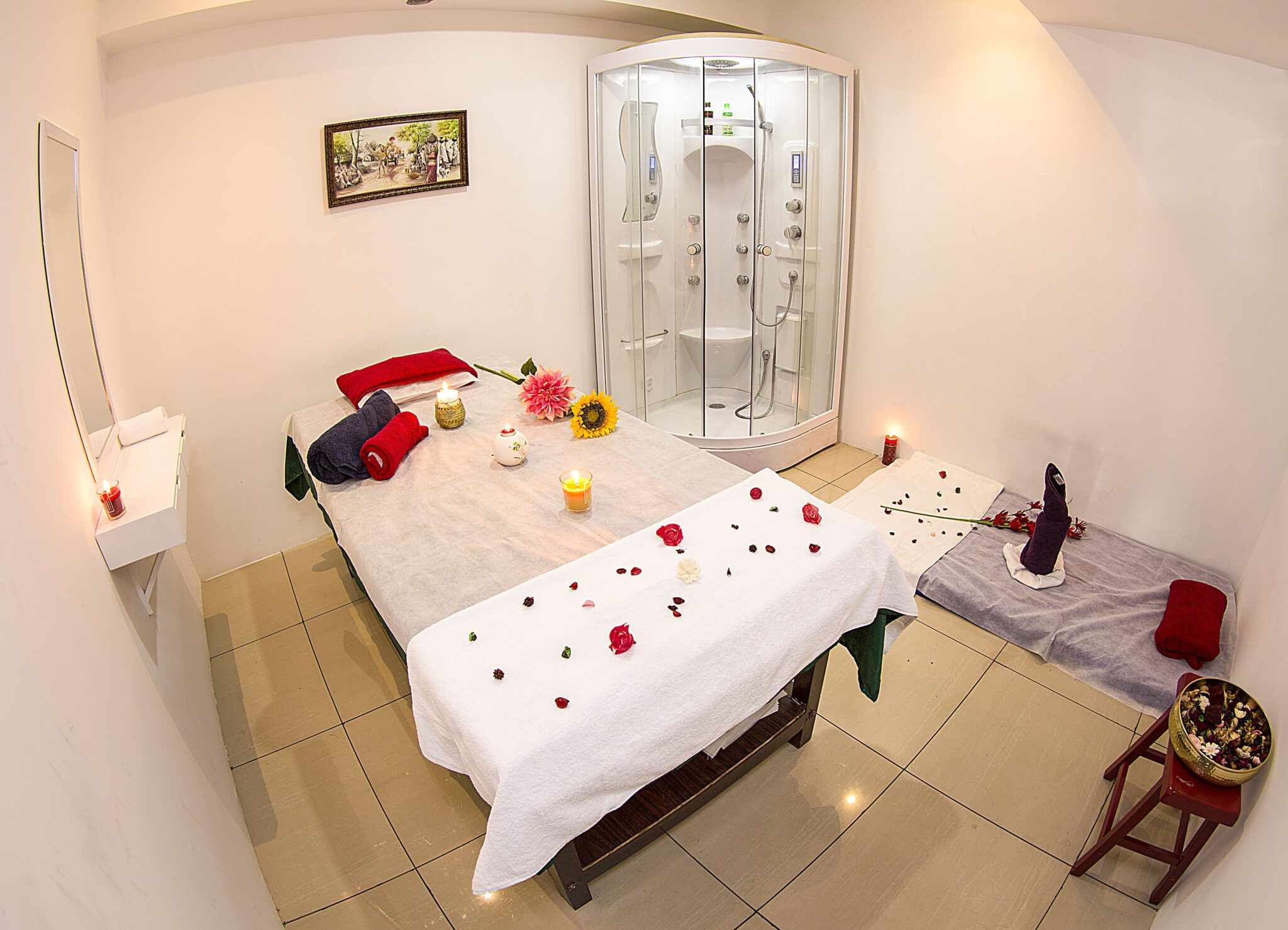 A Full view of the massage room with a beautifully decorated bed with fresh flowers and aromatic candles. The extra Floor bed is also provided at the side of the bed. A separate shower room is attached near the bed for customers convenience. A mild light effect is given in the background to improve the elegance of the spa.
