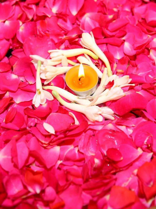 Rose petals beautifully decorated on water with a lighted candle in the middle, surrounded by a layer of white sampangi flowers