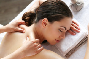 Masseur doing traditional Swedish body massage on the back of a young woman resting head on a white towel in a spa.